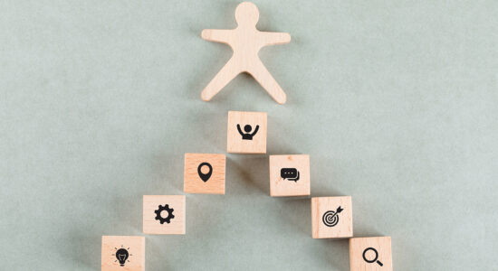 Conceptual of success business with wooden human, rectangle blocks on sage color background flat lay. horizontal image